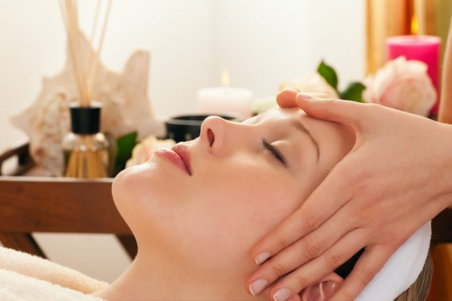 Beautiful woman enjoying a face massage competently carried out in a spa - in the background lots of accessories