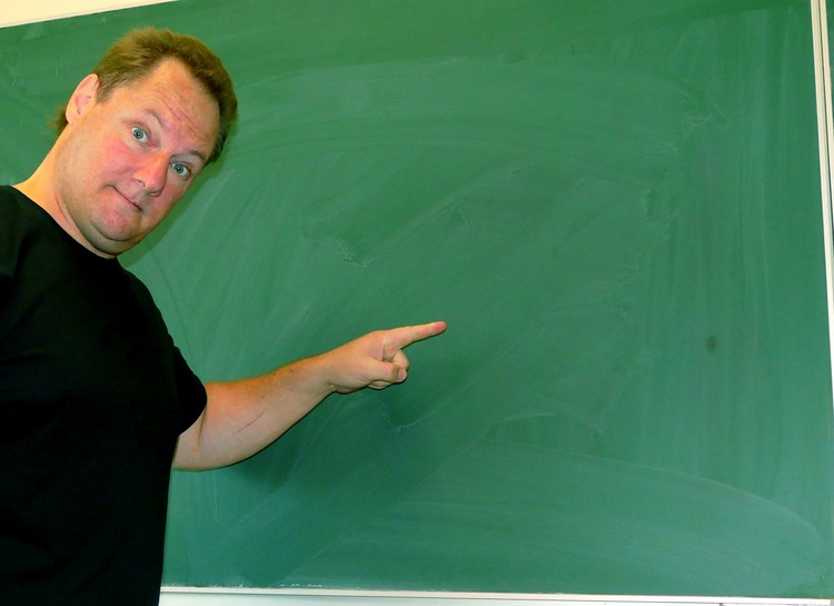 man pointing at a chalkBoard