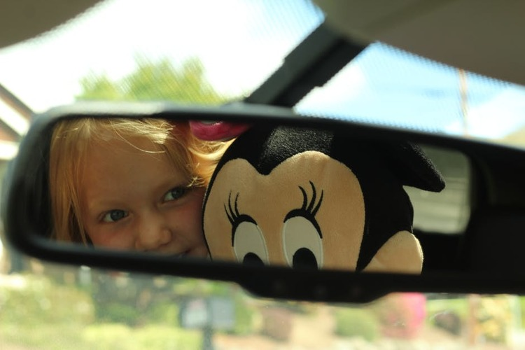 child in rear view mirror car