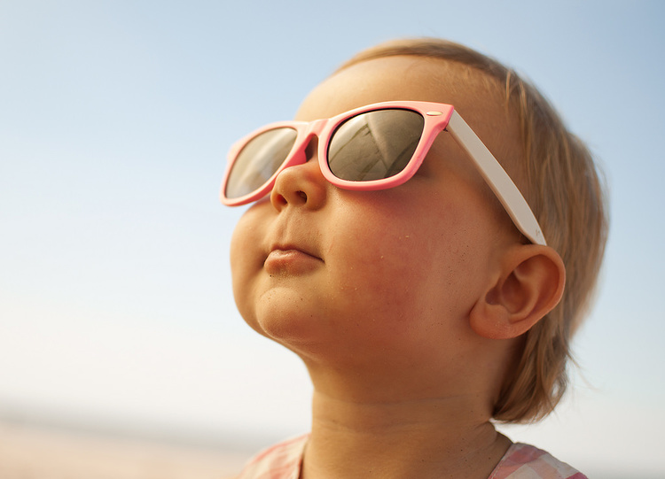 child in sunglasses looking at the sun