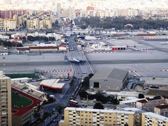 Phía cuối là một bến cảng và hai bên sườn bị bao bọc bởi khu dân cư đông đúc và nhiều núi, đường băng ở sân bay Gibraltar, Vương quốc Anh, còn cắt ngang đại lộ Winston Churchill.