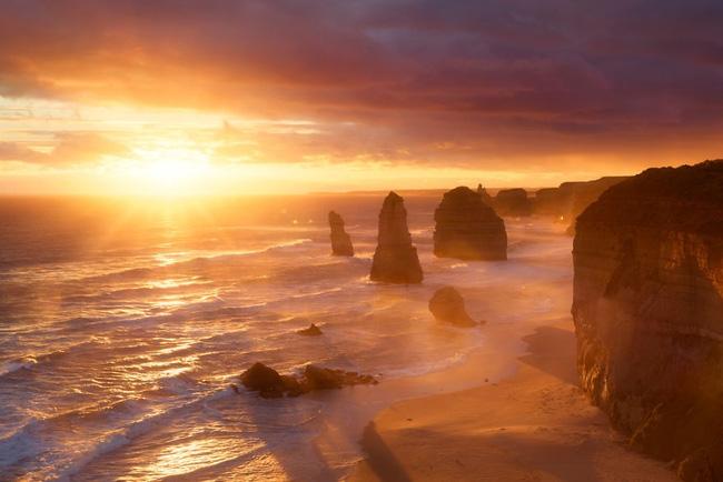 3. Bờ biển Úc vừa mờ ảo, vừa rực rỡ dưới ánh bình minh chói lòa. Thủy triều lên xuống và những tảng đá đen tĩnh lặng rải rác khiến không gian có chút gì đó kỳ bí khó tả.