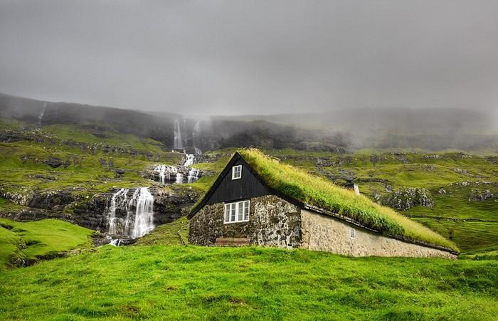 Ngôi nhà làm bằng đá và lợp mái cỏ nằm bên cạnh một thác nước thuộc hòn đảo đẹp như tranh vẽ củaStreymoy,Saksun, quần đảoFaroe.
