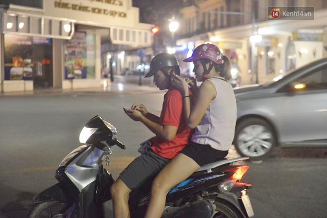 Một cặp đôi say sưa ngồi chơi Pokemon trên xe máy.