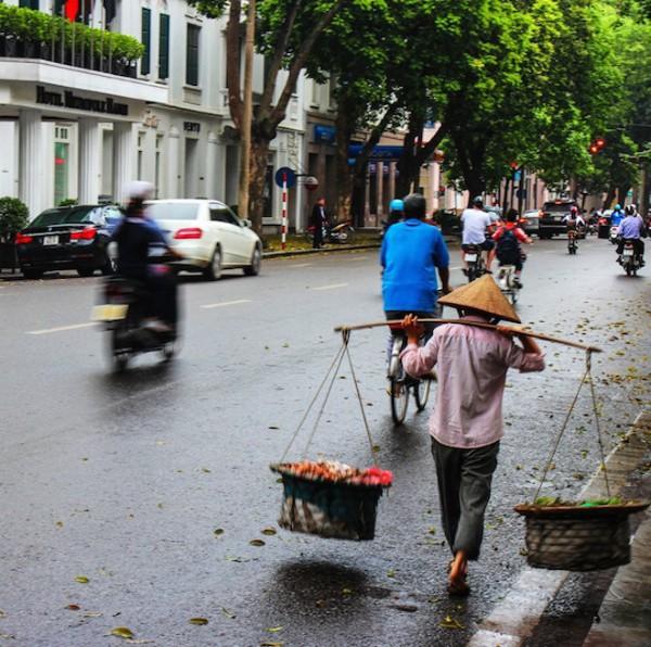 """""""Kinh tế Việt Nam phát triển mạnh mẽ. Bằng chứng là tôi có thể dễ dàng bắt gặp trên đường những chiếc BMW, Mercedes đời mới nhất hay cả xe Rolls Royce đắt tiền. Tuy nhiên hình ảnh khiến tôi nhớ mãi lại là người phụ nữ đội nón lá đang mải miết với gánh hàng rong trong buổi sáng ẩm ướt của Hà Nội""""."""