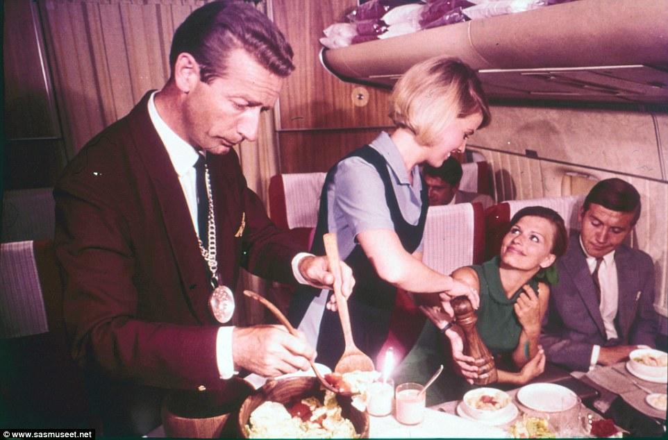 Một nữ tiếp viên hàng không đang rắc tiêu lên phần ăn cho khách trong khi người phục vụ khác trộn salad. Bức ảnh chụp vào những năm 1960.