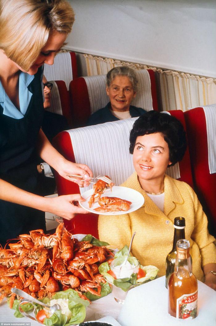 Một hành khách được phục vụ tôm hùm Na Uy cùng rượu khai vị được đặt trên bàn.