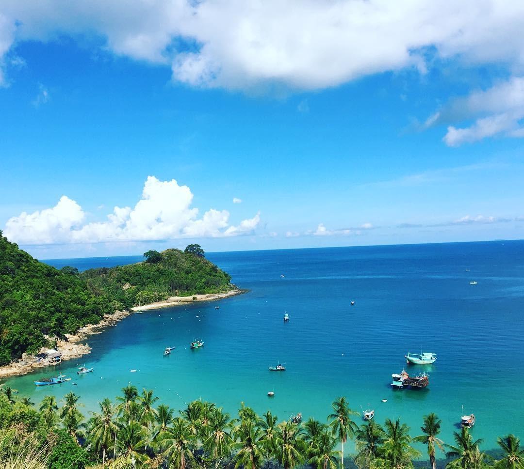 Nước biển xanh ngắt được bao bọc bởi những hàng dừa xanh soi bóng