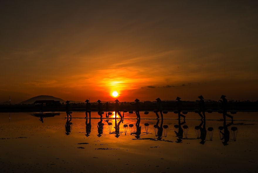 Ánh nắng lấp loáng soi bóng những người nông dân làm muối ở Nha Trang. Khoảnh khắc được chụp lại bởi nhiếp ảnh gia Arif Kugu.