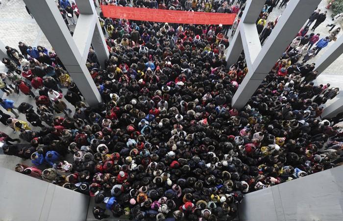 Các thí sinh tập trung tại lối vào một lớp học để tham dự kỳ thi tốt nghiệp kéo dài 3 ngày ở Hợp Phỉ, tỉnh An Huy. 1,8 triệu người đã tham gia kỳ thi này năm 2013.