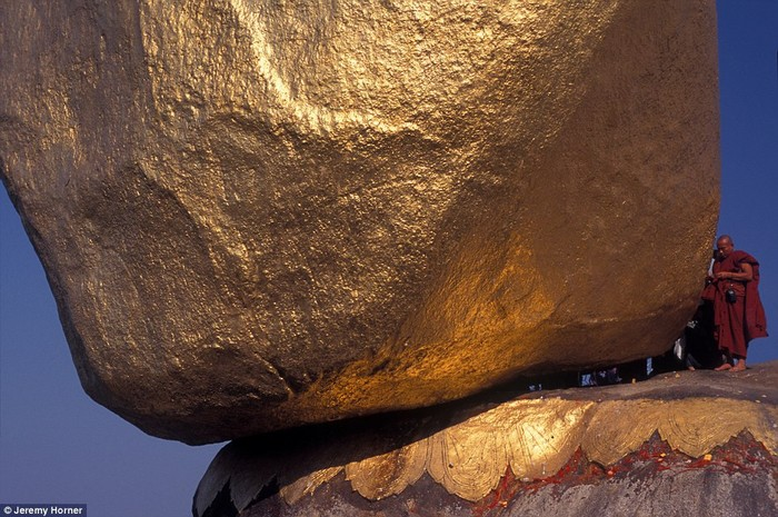 Một nhà sư bên cạnh Đá Vàng nổi tiếng. Người ta đồn rằng một sợi tóc Phật chính là thứ đã giữ hòn đá tưởng chừng phá vỡ mọi nguyên tắc trọng lực này đứng chắc chắn trên mép núi chênh vênh.