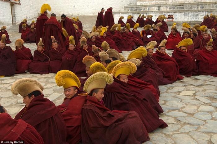 Các nhà sư tại trường Phật giáo Gelugpa ở Tây Tạng, đội mũ vàng đặc trưng của họ và chờ đợi bên ngoài hội trường cầu nguyện chính của tu viện Labrang.