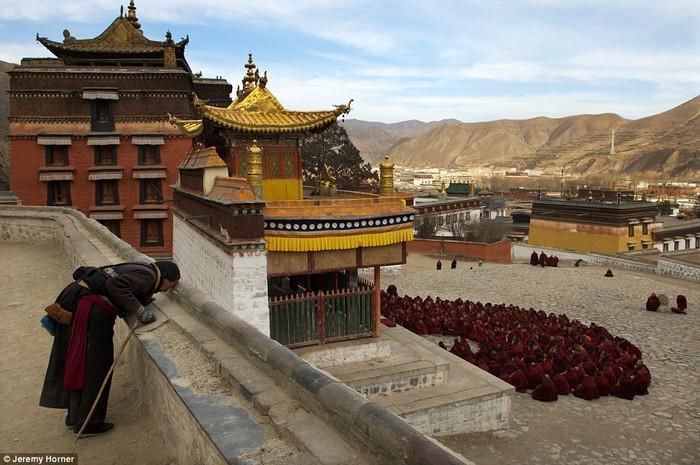 Một khách hành hương dừng lại cầu nguyện trong lúc đám đông các nhà sư đang tập trung ngoài sảnh chính tu viện Labrang.