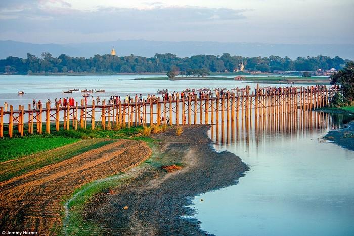 Các nhà sưu đi qua cây cầu U Bein, bắc ngang qua hồ Taungthaman gần Amarapura, Myanmar. Cây đầu xây năm 1850 được cho là cây cầu gỗ tếch lâu đời và dài nhất thế giới.