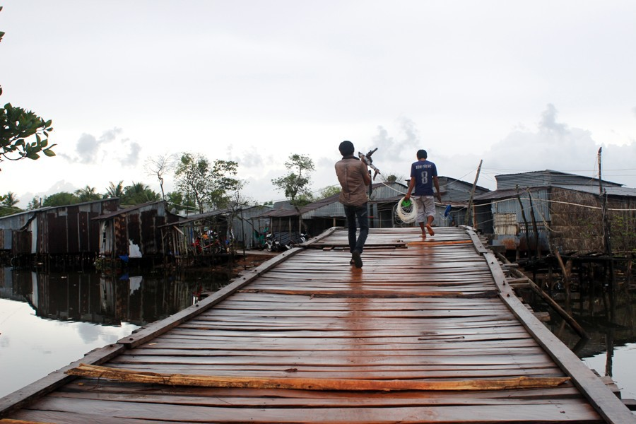 Con đường vào Bãi Cửa Cạn quanh co trên chiếc cầu gỗ cùng những ngôi nhà tạm bợ mang phong cách miền tây sông nước.
