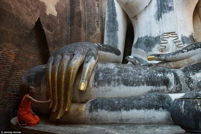 Một nhà sư chạm tay vào bức tượng Phật khổng lồ tại chùa Wat Si Chum, Thái Lan.