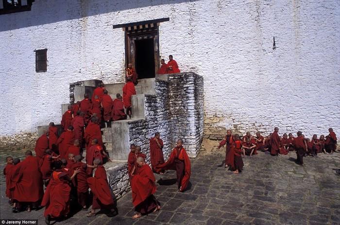 Trong những chiếc áo choàng màu đỏ rực rỡ, các nhà sư trở lại cầu nguyện sau giờ nghỉ trong sân tu viện Semtokha gần Thimphu, Bhutan.