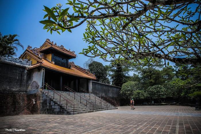 Khiêm Cung Môn bề thế, trước cửa có nhiều cây đại được trồng hài hòa với khung cảnh.