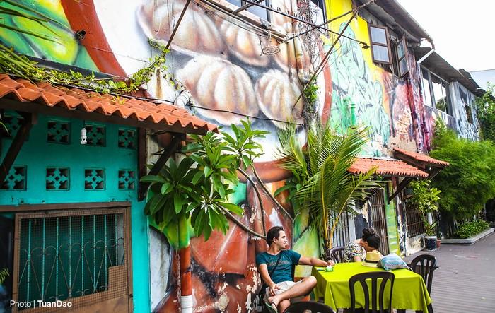 Du khách nghỉ chân bên cạnh những bức tường được trang trí bằng các hình ảnh đồ ăn sống động.