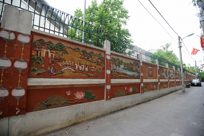 Bức tường được chia thành hai phần, phần trên là các bức tranh khổ lớn về phong cảnh non nước, làng quê hoặc đàn cá…