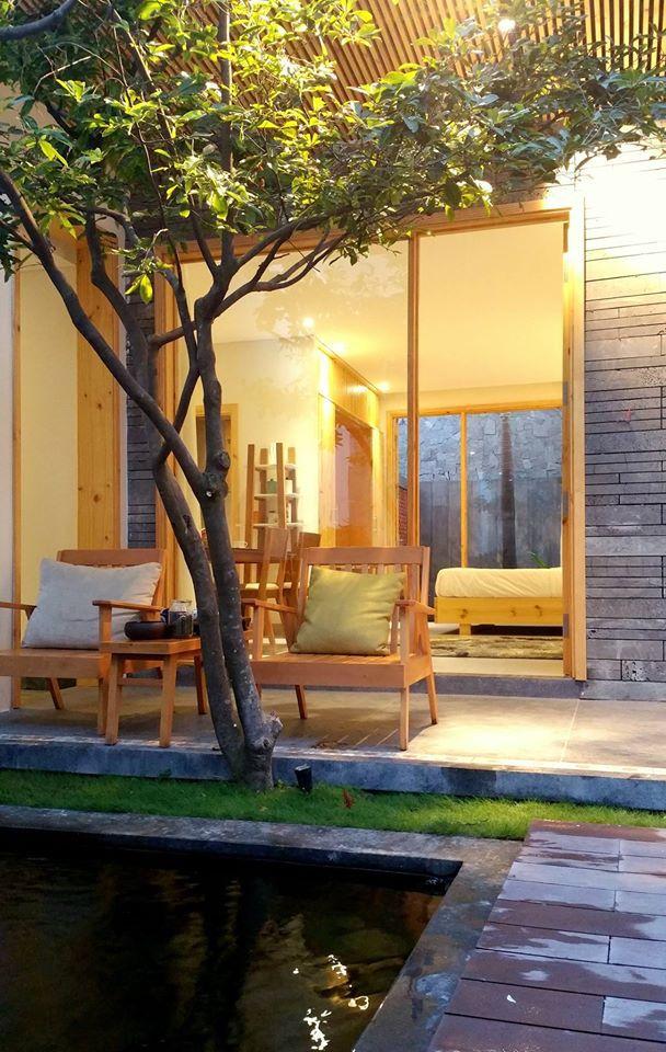 Phòng nghỉ với tầm nhìn lãng mạn ra bên ngoài có cây xanh và hồ nước, cùng bộ bàn ghế để đọc sách, trò chuyện...