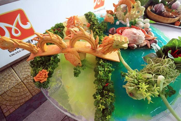 Những bàn tiệc có món lẩu cũng được chú trọng trang trí bàn rau sống nhằm tạo ấn tượng cho người thưởng thức. Hình ảnh cầu Rồng ở Đà Nẵng được nhiều đầu bếp chọn để tạo hình từ quả bí đỏ.
