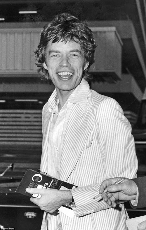 Mick Jagger cười tươi khi nhìn thấy các ống kính máy ảnh.