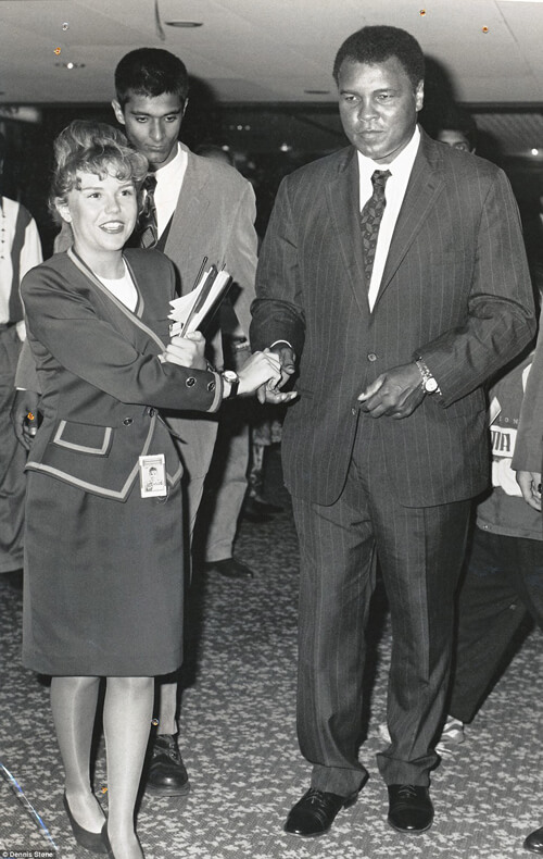 Huyền thoại quyền Anh Muhammad Ali (bên phải) đang được nhân viên sân bay dẫn đi một lối khác theo diện ưu tiên.