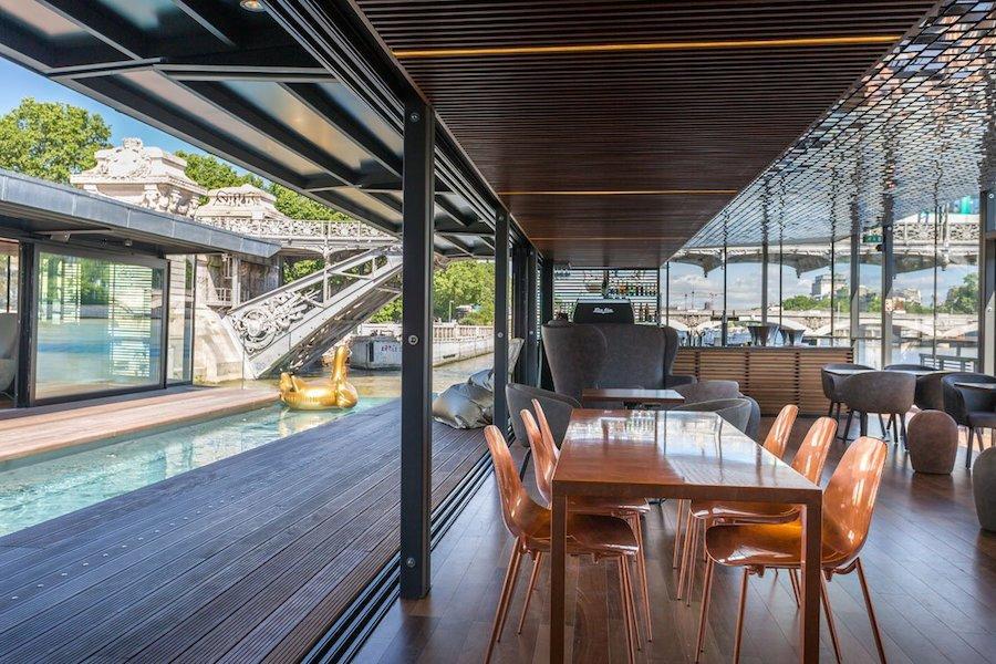 Khu vực quầy bar quanh bể bơi thiết kế theo hướng không gian mở vào mùa hè và lắp kính bao quanh để ngăn gió lạnh trong mùa đông.