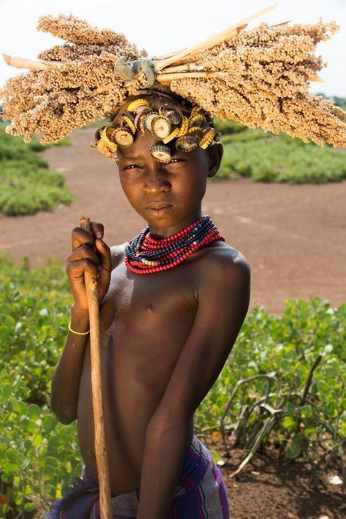 Massimo cho biết, để có tiền khi chụp ảnh, những người phụ nữ còn đeo thêm hoa, sừng hay các loại lọ... lên đầu. Trẻ em thì tạo dáng giống người mẫu có kinh nghiệm và còn trang trí bằng màu vẽ hay các hành động nhảy múa. Trong ảnh là một cô bé ở bộ tộc Dassanech.