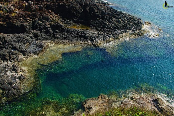 Gành Hố Chảo nằm dưới chân Gành Yến với những khối đá đen thẫm như tàn tích núi lửa ở Lý Sơn, cùng những vũng biển xanh như ngọc bích.