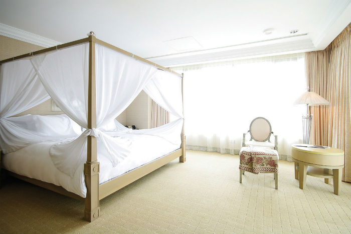 Hệ thống cửa kính lớn đón sáng tự nhiên vào trong phòng nhưng vẫn tạo cảm giác riêng tư nhờ rèm phủ. Chiếc giường lớn đặt trong phòng cùng các vật dụng đơn giản.