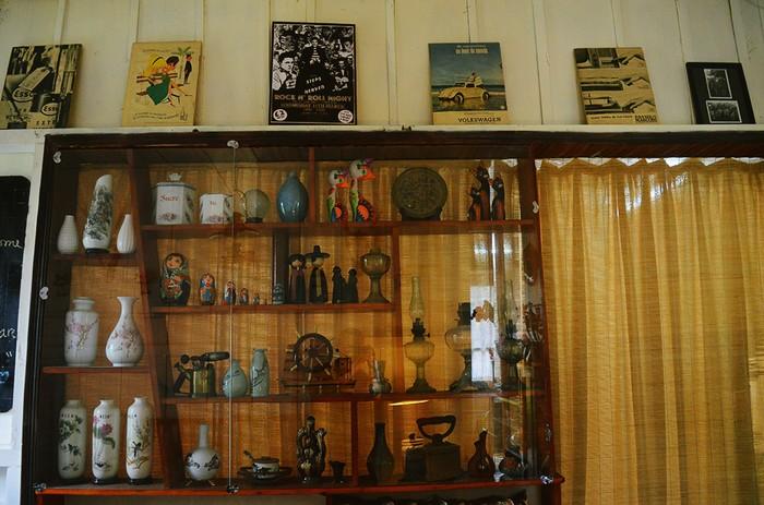 Trên bức tường cạnh lối đi, quán bày trí những đồ vật cũ trong một chiếc tủ kính. Bạn sẽ bắt gặp những tờ tạp chí, tranh ảnh đã rất cũ.