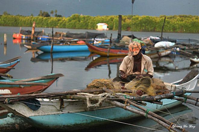Ngư dân này đang gỡ lưới đánh cá trên chiếc thuyền nhỏ bé của mình trong ánh nắng chiều phớt nhẹ.