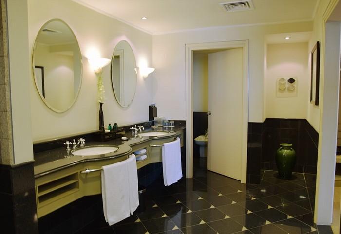 Phòng tắm có thiết kế tông màu đen kết hợp ánh sáng đèn vàng tạo cảm giác ấm cúng nhưng vẫn sang trọng.