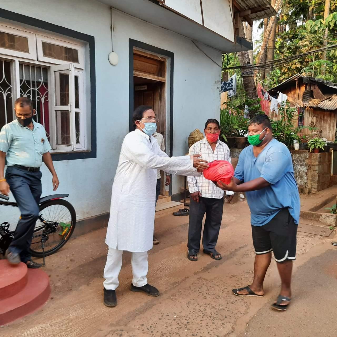 पणजी में मोटरसाइकिल चालकों को आवश्यक सामान वितरित करते आयुष मंत्री