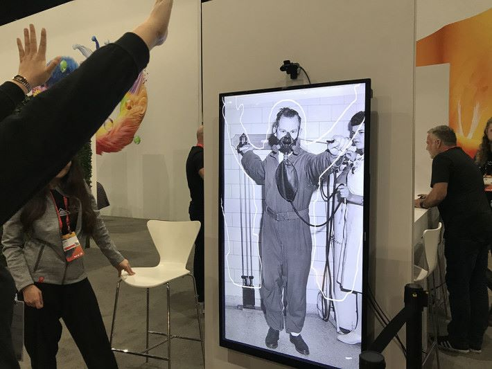 另一個現場示範是透過一個視像鏡頭,感測用家的動態功能,例如圖中示範者同時舉起雙手,Sansai 就能夠辨認到類似動作,在於圖片庫中找出最適當的畫面展示出來。