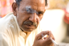 A man smoking in the slums of India.