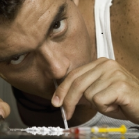 A man in a white tank top sniffs what appears to be cocaine