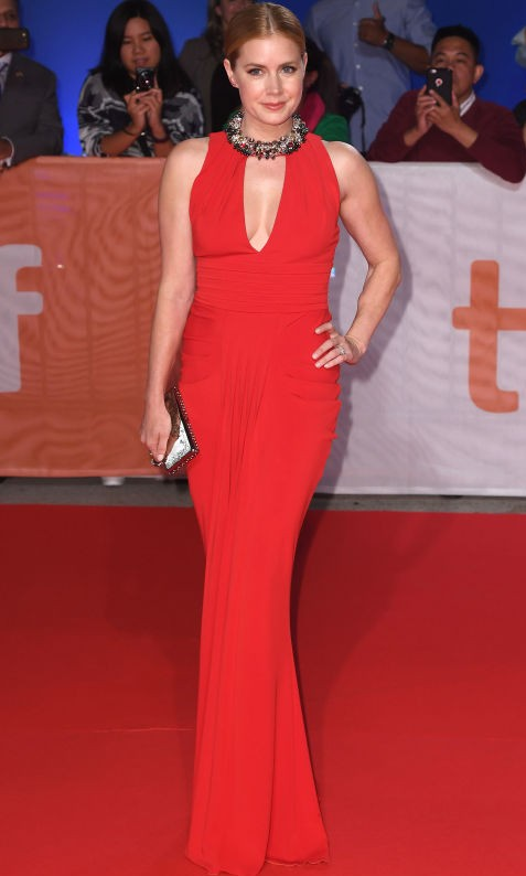 Stunning in red, Amy Adams poses for photographs on the red carpet at her new film