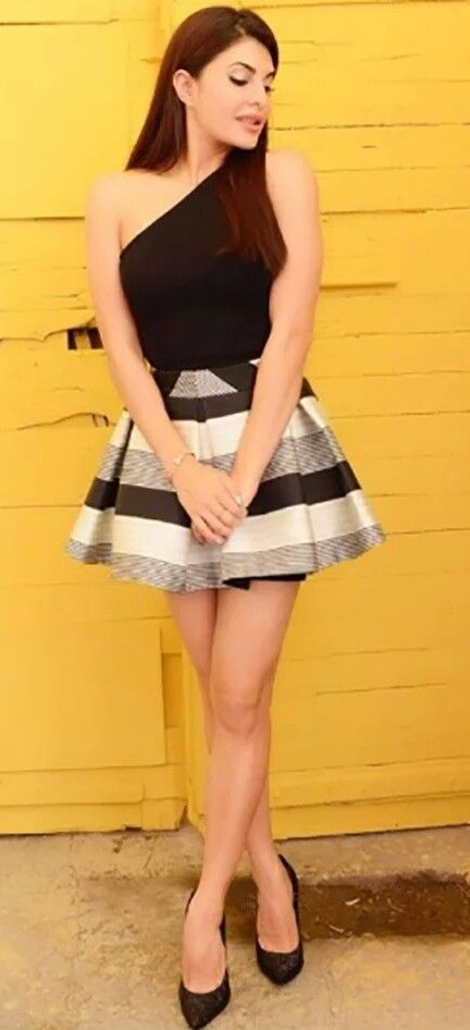 Jacqueline is flaunting the outfit with a pair of blacktop and the stripped skirt. - SeenIt