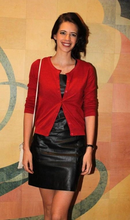 I want the black leather mini dress that Kalki Koechlin is wearing along with the red cardigan. - SeenIt