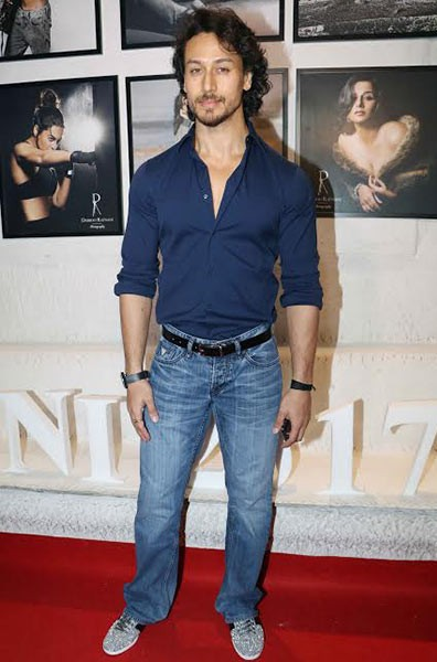 Want the entire outfit that Tiger Shroff is wearing. Navy blue shirt, blue jeans and grey shoes. - SeenIt
