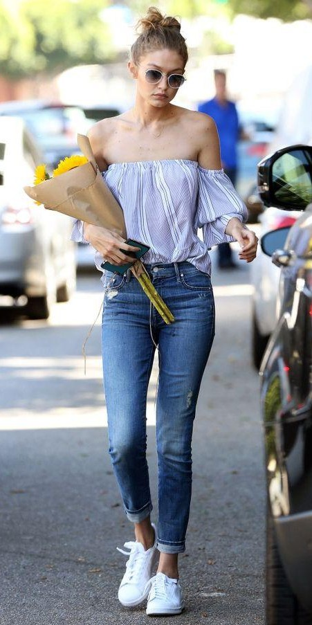 Looking for Gigi Hadid's blue and white striped off shoulder top, blue denims and white sneakers - SeenIt