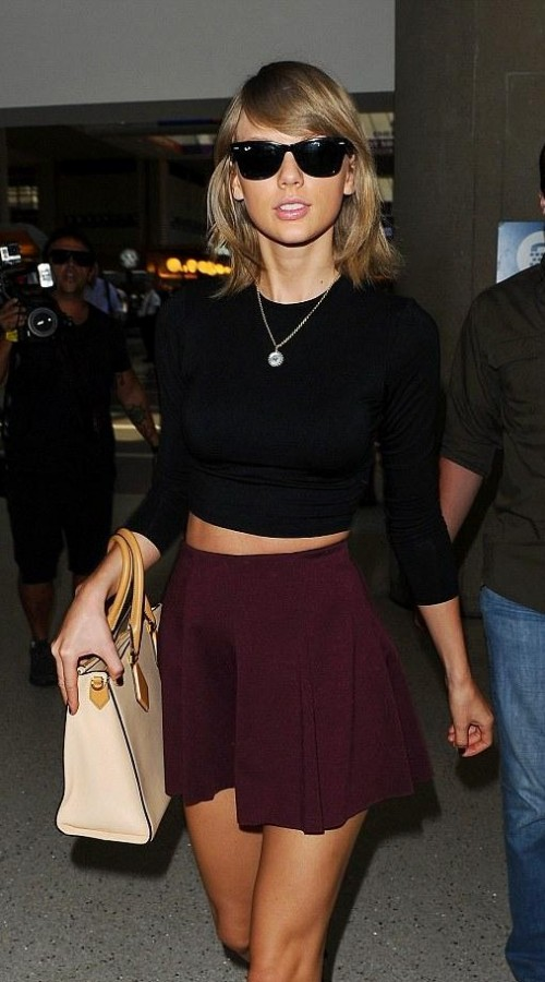 Looking for a similar burgundy flared mini skirt, black crop top and wayfarer sunglasses that Taylor Swift is wearing. - SeenIt