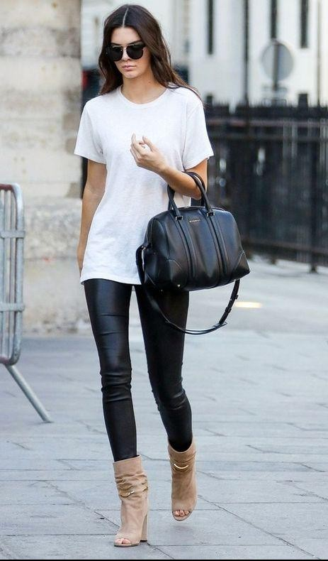 Looking for Kendall Jenner's black leather pants and white casual top along with the black top handle bag. - SeenIt