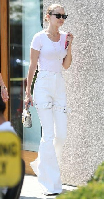 Help me find a similar white flared pants like Gigi Hadid is wearing along with the top and a similar black cateye sunglasses. - SeenIt