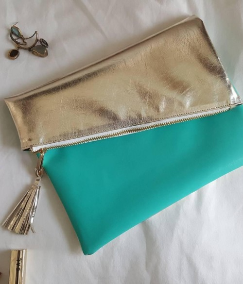 Help me find a this silver and teal envelope clutch with tassels. - SeenIt