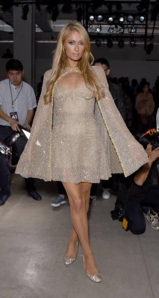 Yay or Nay? Paris Hilton wearing a golden shimmer dress with a cape attends Lanyu fashion show during New York Fashion Week - SeenIt