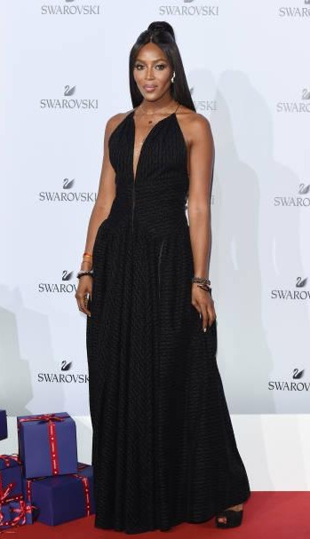 Yay or Nay? Naomi Campbell attends Swarovski Crystal Wonderland Party wearing a plunge neck black gown during the Milan fashion week - SeenIt